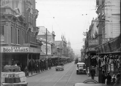 Looking down Cuba Street at the intersection of Ghuznee Street ca 1923-1928. 126 Cuba is the second building on the left, next to what was then the City Boot Store. The original verandah and balconies on the second and third floors are visible. On the opposite side of the road is Hotel Bristol and Carter & Co. (This section of the Hotel Bristol was replaced by the Bristol Court in 1982).    Cuba Street, Wellington. Smith, Sydney Charles, 1888-1972 :Photographs of New Zealand. Ref: 1/2-048945-G. Alexander Turnbull Library, Wellington, New Zealand. http://natlib.govt.nz/records/23119940